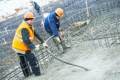 Concreting Arbeit Concreter zwei mit Erschütterungswerkzeug Stockfotos