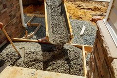 Concreting sidewalk around the house. Pouring cement concrete Stock Image