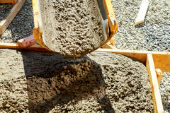 Concreting sidewalk around the house. Pouring cement concrete process to apartment building Royalty Free Stock Image