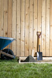 Concreting tools and wheelbarrow in DIY project. Concreting tools and wheelbarrow against a wooden plank fence in a DIY, backyard gardening project Royalty Free Stock Photos