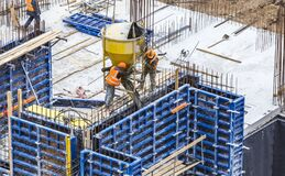 Free Concreting Work At The Construction Site. Сonstruction Workers Pour Liquid Concrete From Cement Concrete Hopper To Fromwork Stock Photo - 181651970