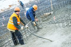 Concreting work. Two concreter with vibration tool. Concreting work. construction site worker during pouring and vibrating concrete into formwork at building Stock Photos