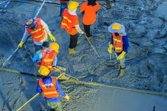 Concreting workers are leveling poured liquid concrete on a stee. L reinforcement to form strong floor slabs Stock Photo