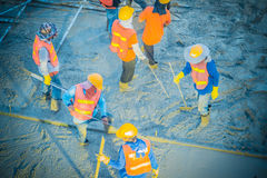 Concreting workers are leveling poured liquid concrete on a stee. L reinforcement to form strong floor slabs Royalty Free Stock Photo