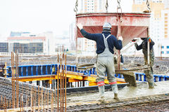 Concreting works. Concreting work: construction site worker during concrete pouring into formwork at building area with skip Stock Photo
