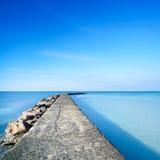 Concreto e rochas cais ou molhe na água azul do oceano Fotografia de Stock