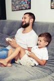 Concurrence de jeu vidéo à la maison entre le père et son petit fils Photo stock