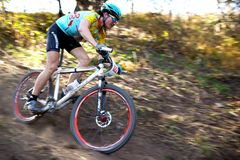 Concurrence de vélo de montagne dans la forêt d'automne Photos libres de droits