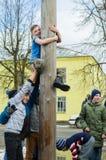 Concurrence nationale russe en montant un poteau en bois en hommage à la fin de l'hiver dans la région de Kaluga le 13 mars 2016 Photographie stock libre de droits