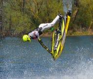 Concurrent de Jet Skier de style libre exécutant le saut périlleux arrière créant au sort de jet Image stock