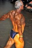 Concurrent masculin de bodybuilding montrant sa pose de dos de meilleur Photographie stock libre de droits