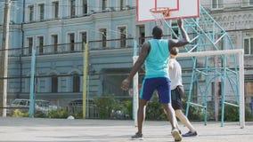 Concurrerende basketbalspelers die bal druppelen bij hof, actieve levensstijl, sporten stock videobeelden