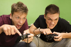 Concurrerende broers die grappige videospelletjes spelen royalty-vrije stock afbeeldingen