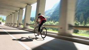 Concurrerende die fietser van erachter in onderdoorgang met pijlers wordt geschoten stock videobeelden