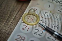 Condón en el calendario Imagen de archivo libre de regalías