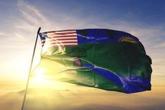 Condado do rio Gee da tela de pano de matéria têxtil da bandeira de Libéria que acena na névoa superior da névoa do nascer do sol ilustração do vetor