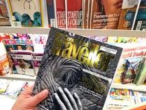 Conde Nast-Reizigerstijdschrift in een hand stock afbeeldingen