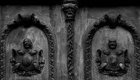 The condemned. Shot in black and white, detail on an wood sculpture representing two condemned, placed on the door of this historic building, set in Logroño, La Royalty Free Stock Images