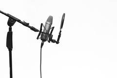 Condensador Mic On Stand In Studio aislado en blanco Imágenes de archivo libres de regalías
