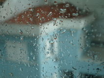 Condensation. Window of glass with raindrops and blue house behind. Blur image Stock Photos