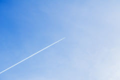 Condensation track of airplane flying high against in clear blue sky. With place for your text for modern background stock images