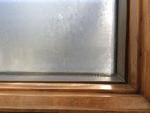 Condensation on wood window frame. Condensation and waster has built up on this glass window, forming beads of water and steam. A wood window frame inside a Royalty Free Stock Image