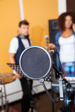 Condenser With Band Members In Background. Closeup of condenser with band members in background at recording studio Stock Images