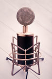 Condenser Microphone. Large diaphragm condenser microphone on a wooden table Stock Image
