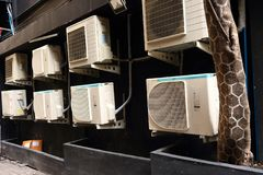 Condensing units. Group of condensing units of air conditioners fixed to the wall behind building, selective focus stock image