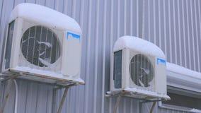 Condicionador de ar exterior na rua na neve Os f?s s?o atr?s das barras filme
