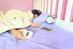 Condicionador de ar remoto da posse da mão da jovem mulher e sono no fotografia de stock royalty free