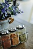 Condiment set with a vase of flowers on the table royalty free stock photo