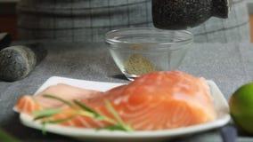 Condimentando y cocinando los pescados de color salmón con arroz y el pepino metrajes