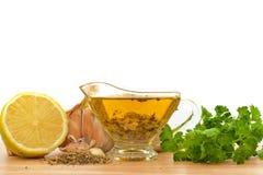 Condimento dell'insalata con l'olio, l'aglio ed il limone di oliva Fotografia Stock