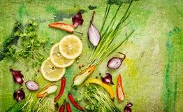 Condimento y especias frescos para cocinar en el fondo verde, visión superior imagenes de archivo
