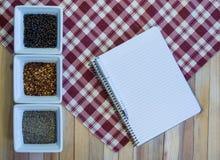 Condimentos de la pimienta y cuaderno en blanco Imagenes de archivo