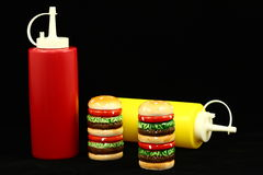 Condiments. Plastic ketchup and mustard bottles, and a set of hamburger shaped salt and pepper shakers photographed on a black background Royalty Free Stock Image