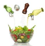 Condiments de versement sur une salade colorée. image stock