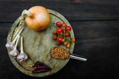 Condiments i pikantność dla kreatywnie kucharstwa na ciemny nieociosany drewnianym Fotografia Stock