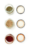 Condiments jars on white Royalty Free Stock Photos