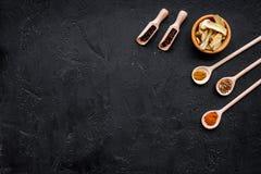 Condiments, podprawy i pikantność pojęcie, Suche pikantność w drewnianych łyżkach na czarnej tło odgórnego widoku kopii przestrze Zdjęcia Stock