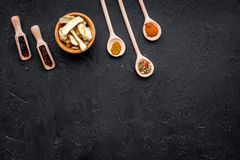 Condiments, podprawy i pikantność pojęcie, Suche pikantność w drewnianych łyżkach na czarnej tło odgórnego widoku kopii przestrze Fotografia Stock