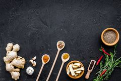 Condiments, seasoning and spices concept. Dry spices in wooden spoons near ginger, rosemary, chili pepper on black. Background top view Royalty Free Stock Photo