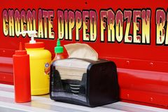 Condiments on Shelf on the Side of a Food Truck with a Sign Advertising Chocolate Dipped Frozen Bananas Royalty Free Stock Photography