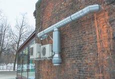 Condizionamento d'aria e tubi metallici su un muro di mattoni Fotografia Stock