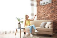 Condizionatore d'aria di funzionamento della donna mentre sedendosi sul sofà fotografia stock