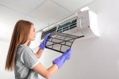 Condizionatore d'aria di pulizia della giovane donna, fotografia stock libera da diritti