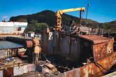 Condizione arrugginita abbandonata della nave vicino al pilastro fotografia stock libera da diritti
