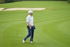 Condizione asiatica ed orologio del giocatore di golf dopo avere messo sul verde nel campo da golf Fotografia Stock Libera da Diritti