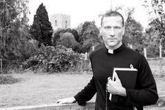 Condizione bella del sacerdote accanto al portone del paese mentre tenendo la sua bibbia con la chiesa e campo nel fondo immagine stock libera da diritti